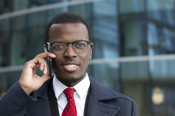 Horizontal portrait of young dark-skinned business guy dressed in formal clothes while standing in street in city center having discussion on cellphone, looking attentive and focused on news he hears