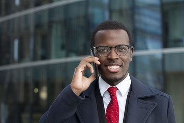 Outdoor headshot of African American businessman talking on phone in street discussing important business matters or family issues with happy smile, feeling confident and relaxed, enjoying free time