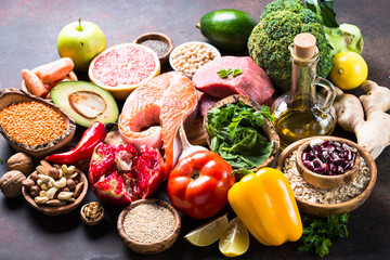 Balanced diet food background. Organic food for healthy nutrition, superfoods. Meat, fish, legumes, nuts, seeds, greens, oil and vegetables.