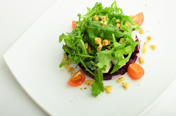 Salad with beet, cheese, cherry tomatoes, arugula and walnut on a plate isolated on white background