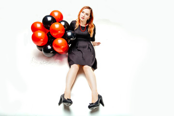 Strange sad woman in black dress holding black and red balloons and sitting like a doll on white floor background.