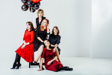 Full body portrait of five serious woman in black and red dress sitting together and looking up at red and black balloons over white loft background. Celebrate, date, fun, hen-party concept.