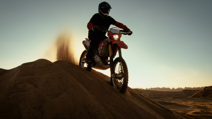 Professional Motocross Rider on FMX Motorcycle Stands on the Sand Dune and Overlooks Off-Road Track, then Drives Down.