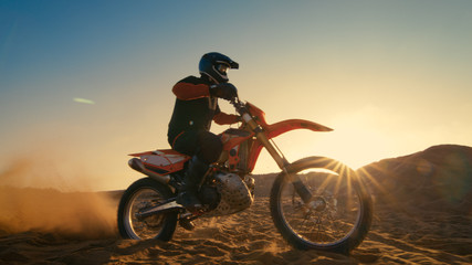 Low Angle Shot of the Professional Motocross Driver Riding on His FMX Motorcycle on the Extreme Off-Road Terrain Track.