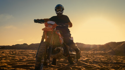 Front View Shot of the Professional Motocross Driver Saddles His FMX Dirt Bike on the Sand/ Dirt Track.