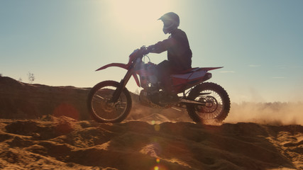 Side View Footage of the Professional Motocross Motorcycle Rider Driving on the Dune and Further Down the Off-Road Track. It's Sunset and Track is Covered with Smoke/ Mist.