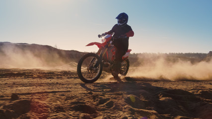 Side View Footage of the Professional Motocross Motorcycle Rider Driving on the Dune and Further Down the Off-Road Track. It's Sunset and Track is Covered with Smoke/ Dust/ Dirt.