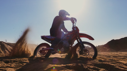 La pose en embrasure Motocyclette Professional Motocross FMX Motorcycle Rider Drives in Circles on the Off-Road Deserted Quarry.