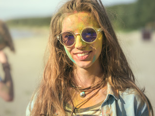 Close-up Portrait of a Beautiful Young Girl with Sunglasses Standing in the Crowd of People Celebrating Holi Festival. Her Face and Clothes are Covered with Colorful Powder.