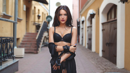 Passionate young girl in sexy lingerie posing at the background of old street.