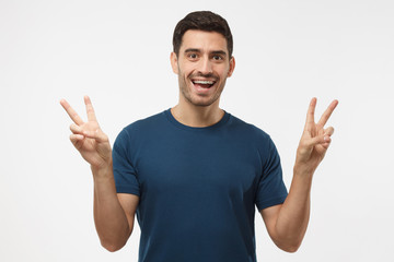 Indoor portrait of young male isolated on gray background in casual clothes with optimistic smile, showing victory sign with both hands, looking friendly and willing to welcome and communicate