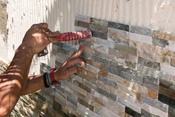 Albañil alicatando un muro con piedra.