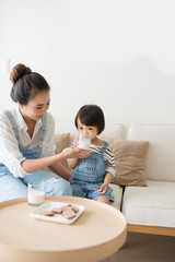 Happy family of asian mom is drinking milk with her cute daughter in the morning at home