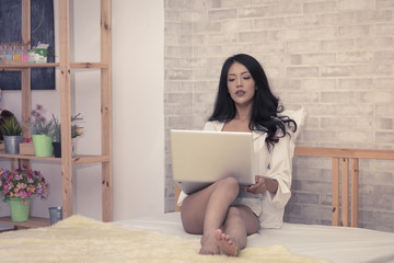 sexy asian woman using laptop on bed
