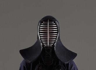 male in tradition kendo armor wearing helmet.