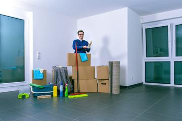 Mann will helle, leere Luxuswohnung reinigen. Dazu zieht er Gummihangschuhe an.