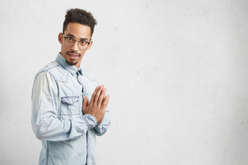 Sideways portrait of confident male with curly hair, oval face, wears denim shirt, keeps palms together as tries to concentrate before reasponsible important task or work, looks directly at camera