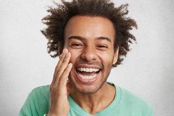 Positiveness and pleasant emotions concept. Glad man with dark healthy skin grins at camera, being happy to be praised by someone, feels proud of himself, poses in white studio. Overjoyed guy