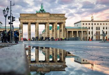 Das Brandenburger Tor in Berlin mit Spiegelung im Regenwasser bei Sonnenuntergang