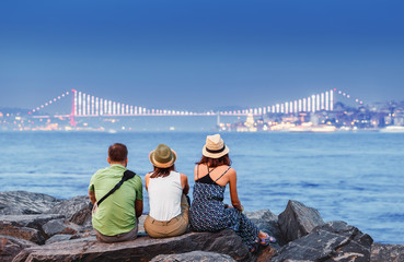 Young friends student or travelers in hat enjoying great view of the Bosphorus Bridge and seascape in Istanbul, vacation concept