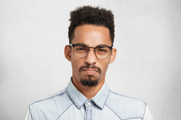Studio portrait of grumpy stylish young man frowns face with dissatisfaction, has bad mood, feels furious and annoyed with something. Pissed off angry Afro American male poses against white wall