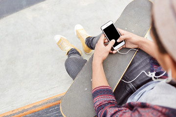 Cropped shot of fashionable teenager wears sport shoes and jeans, holds skateboard, uses modern smart phone for communication with friends and listens songs on white earphones. Leisure concept