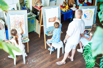 High angle portrait of three children painting on easels during art class and teacher watching them in cozy studio decorated with plants