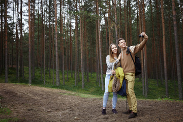 Cheerful young couple boy and girl tourists wearing hiking clothes and carrying backpacks smiling happily while taking self portrait on camera, standing on trail in forest with pines in background