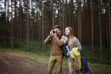 Outdoor portrait of young Caucasian friends boy and girl walking in park or wood together on warm day, male photographer with camera looking for best views and angles, taking pictures of autumn nature
