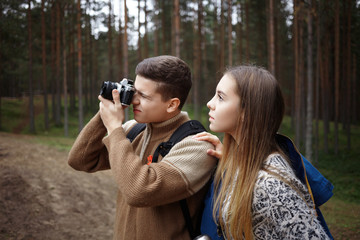 People, trekking, photography, active lifestyle, hobby and leisure. Talented young male photographer taking pictures of beautiful autumn wild nature while hiking in woods together with his girlfriend