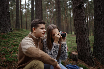 Candid shot of happy beautiful young couple hiking in woods: guy in sweater hugging his girlfriend who is taking pictures using professional camera, shooting amazing autumn nature around them