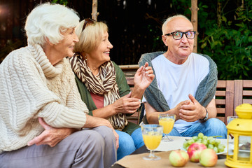 Portrait of three senior people chatting happily telling stories meeting for lunch  on outdoor terrace