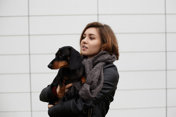 Picture of dachshund dog on hands of beautiful young lady with short hair and pierced nose. Cute teenage girl wearing stylish jacket and woolen scarf carrying her pet dog to vet. People and pets
