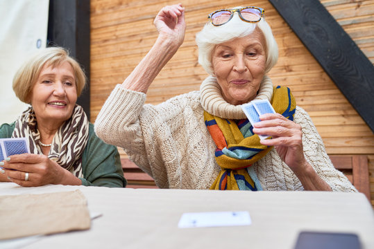 Portrait of cheerful seniors playing card game at lunch table on outdoor terrace, focus on two old women winning game