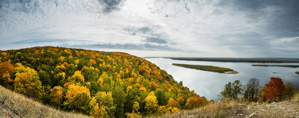 Panoramic view, multicolor autumn forest on hill on riverside of Volga river