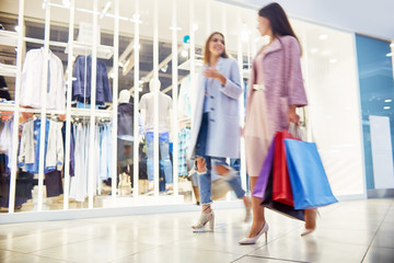 Blurred shapes of two young women walking in shopping  mall chatting happily and smiling holding paper bags with purchases, against background of window displays
