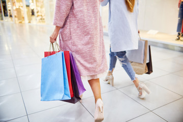 Low section portrait of two young women wearing coats and high heels walking in shopping mall holding paper bags with purchases