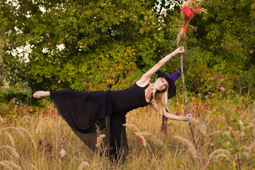 Young girl in witch costume practicing yoga