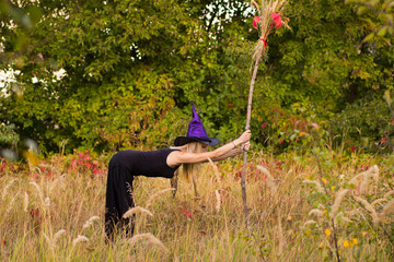 Glad girl in witch costume practicing yoga