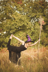 Young girl in witch costume doing fitness
