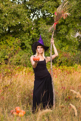 Joyful girl in witch costume with broomstick