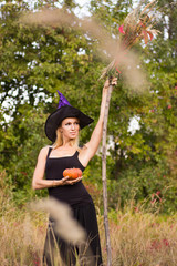 Nice girl in witch costume with broomstick
