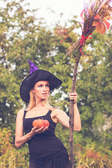 Beautiful girl in witch costume with broomstick