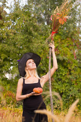 Happy girl in witch costume with broomstick