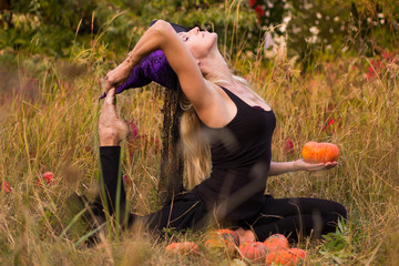 Happy woman in witch costume practicing yoga