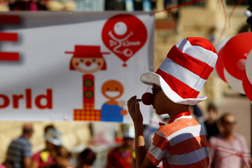A child wears a red nose during the Dr. Klown Kids' Klown Parade during an attempt to set a Maltese record for the largest gathering of clowns and to show solidarity with sick and hospitalised children, in St Julian's