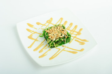 Wakame salad with peanuts and peanut sauce on a plate isolated on white background