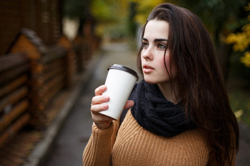 Young woman wearing knitted sweater walking in the autumn park and drinking take away coffee in paper cup. Breakfast on the go.