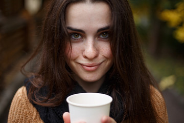 Close up portrait of young pretty smiling woman wearing knitted snood drinking take away coffee in paper cup. Breakfast on the go