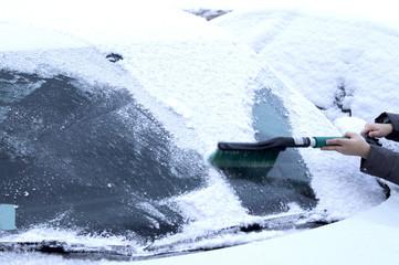 маленький мальчик очищает счёткой стекло автомобиля от снега